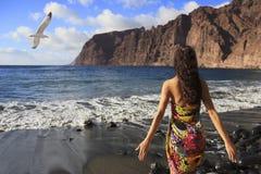 站立在Los Gigantes海滩的美丽的深色的女孩在特内里费岛 图库摄影