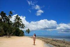 站立在Makaha `海滩海岛n的比基尼泳装的少妇 库存照片