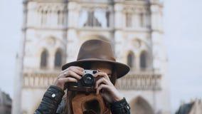 站立在Notre Dame附近在巴黎,法国和拍在减速火箭的影片照相机的年轻美丽的妇女照片 股票视频