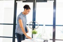 站立在offfice的微笑的美国黑人的办公室工作者画象  免版税库存图片