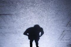 站立在patterened边路的一个人的阴影 库存照片