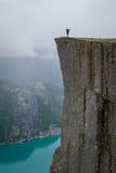 站立在Prekestolen rock& x27的垂直的照片0f游人; s边缘 图库摄影
