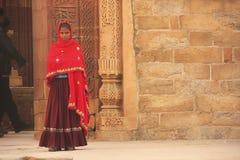 站立在Qutub Minar复合体的五颜六色的礼服的印地安妇女, 免版税库存图片