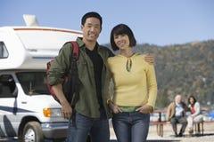 站立在RV前面的夫妇在湖 免版税图库摄影