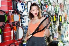 站立在T恤杉的女孩在有球拍的体育用品商店 免版税图库摄影