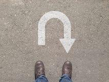 站立在U字型转向标志前面的沥青水泥地板上 免版税图库摄影