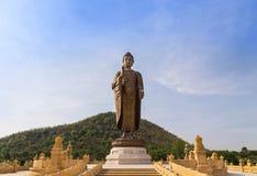 站立在wat thipsukhontharam公开泰国寺庙的大古铜色菩萨雕象 免版税库存照片