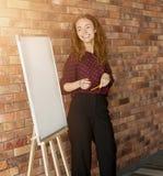 站立在whiteboard的快乐的红头发人妇女 库存照片