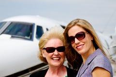 站立外部喷气机的两名妇女 免版税库存照片