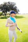 站立女性的高尔夫球运动员举行她俱乐部微笑 免版税库存照片