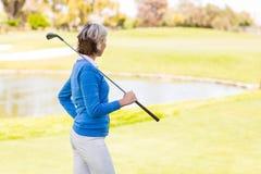 站立女性的高尔夫球运动员拿着她的俱乐部 免版税库存照片