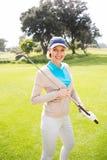 站立女性的高尔夫球运动员拿着她的微笑对照相机的俱乐部 免版税图库摄影