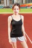 站立女性的athelete放松在看的运动场来了 免版税图库摄影