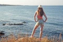 站立妇女的远足者看海岸的海 免版税库存图片