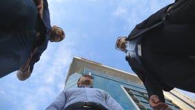 站立室外近的办公室和谈话的低角度观点的三个商人 商人集会和讲话外面  股票录像