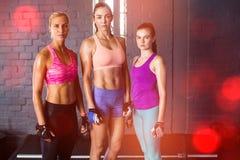 站立对在健身房的墙壁的女运动员 库存照片