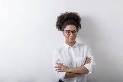 站立对墙壁的微笑的女实业家画象 图库摄影
