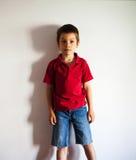 站立对墙壁的男孩 免版税库存图片