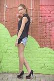站立对墙壁的美丽的女孩 库存照片