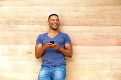 站立对有手机的墙壁的英俊的年轻人 免版税库存图片