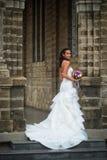 站立对有花婚礼花束的墙壁的新娘  库存图片