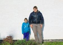 站立对灰泥老外部房子墙壁的十几岁的男孩和小快乐的愉快的女孩由明媚的阳光点燃了 免版税库存照片