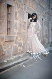 站立对石墙的年轻美丽的印地安妇女户外 免版税图库摄影
