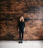 站立对砖墙的帽子的美丽的卷曲女孩 免版税库存图片