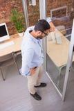 站立对玻璃墙的周道的商人在办公室 免版税库存照片