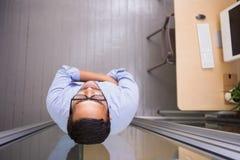 站立对玻璃墙的周道的商人在办公室 免版税库存图片