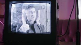 站立小常规黑色电视机监视唱歌的男人和的妇女后边 影视素材