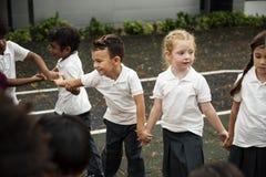 站立小组不同的幼儿园的学生握手 库存照片