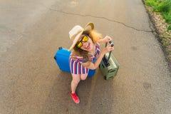 站立带着在路和微笑的手提箱的愉快的快乐的旅客妇女 旅行,假日,旅途的概念 图库摄影