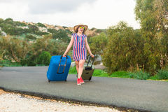 站立带着在路和微笑的手提箱的愉快的快乐的旅客妇女 旅行,假日,旅途的概念 免版税库存图片
