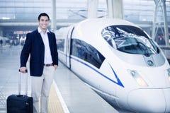 站立带着在铁路平台的一个手提箱的商人在高速火车旁边在北京 免版税库存图片