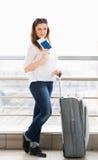 站立带着手提箱的一件白色女衬衫的妇女,在玻璃墙背景中持一本护照在驻地 免版税库存照片