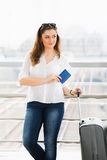 站立带着手提箱的一件白色女衬衫的妇女,在玻璃墙背景中持一本护照在驻地 库存照片