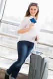 站立带着手提箱的一件白色女衬衫的妇女,在玻璃墙背景中持一本护照在驻地 图库摄影