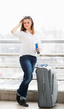站立带着手提箱的一件白色女衬衫的妇女,在玻璃墙背景中持一本护照在驻地 免版税库存图片