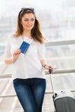 站立带着手提箱的一件白色女衬衫的妇女,在玻璃墙背景中持一本护照在驻地 库存图片