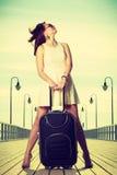 站立带着手提箱,被风吹头发的妇女 免版税库存图片