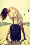 站立带着手提箱,被风吹头发的妇女 库存图片