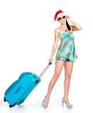 站立带着旅行手提箱的圣诞老人帽子的妇女 库存照片