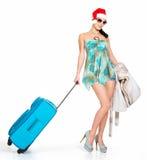 站立带着旅行手提箱的圣诞老人帽子的妇女 免版税库存图片
