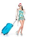 站立带着旅行手提箱的圣诞老人帽子的妇女 免版税库存照片