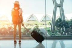 站立带着行李或手提箱的青少年的亚裔妇女在窗口 免版税库存照片