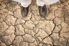 站立干燥破裂的地球上的人 库存图片
