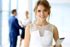 站立平直和smilling在办公室的女商人 免版税库存图片