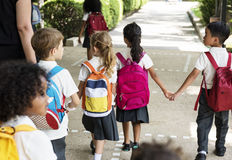 站立幼儿园的学生握手 库存照片