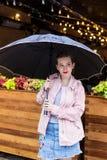 站立开放桃红色的雨衣的少妇耐心地等待在伞下 库存图片